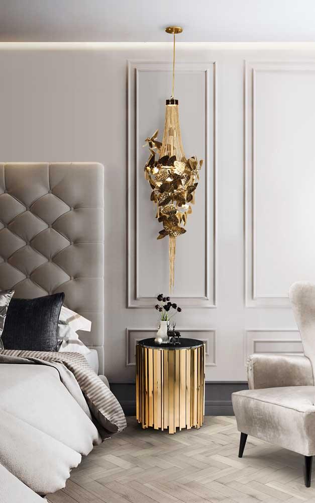 Maravilhosa composição entre o lustre candelabro dourado, o criado mudo moderno e a parede com boiserie