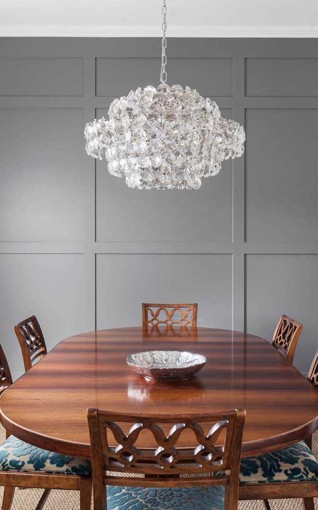Nessa sala de jantar, o destaque da decoração fica por conta do brilhante lustre candelabro sobre a mesa