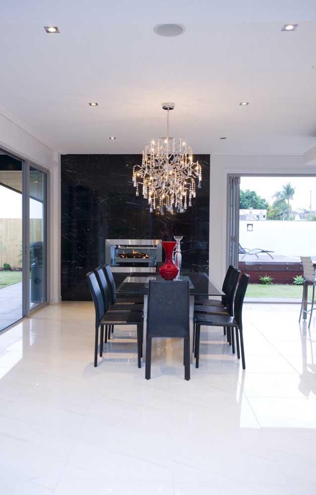 A sala de jantar clean e elegante apostou em um lustre candelabro para preencher o ambiente