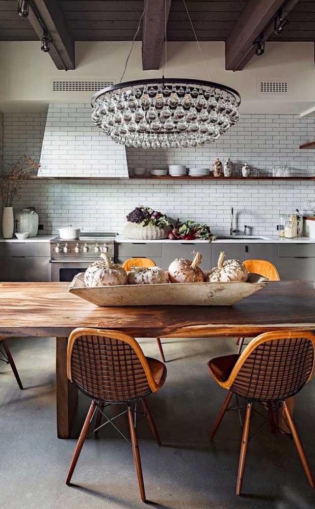 Diferentes estilos de decoração passeiam por essa cozinha, a começar pelo lustre candelabro de cristal