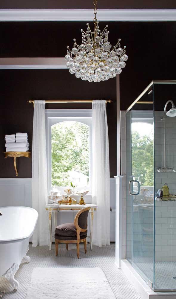 As paredes pretas desse banheiro deixaram o lustre candelabro ainda mais em evidência
