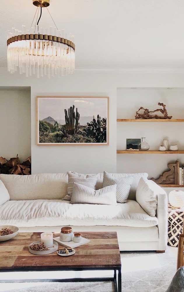 Use o lustre candelabro para destacar um móvel ou área do ambiente, como nessa imagem, em que a peça chama a atenção para o centro da sala