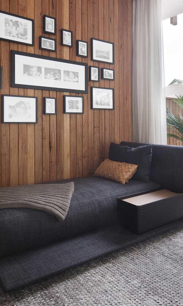 A parede revestida com madeira ajuda a destacar a chaise longue preta