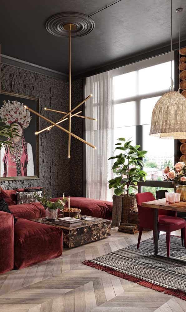 Composição elegante e ousada entre o sofá vermelho e os detalhes em preto da sala de estar