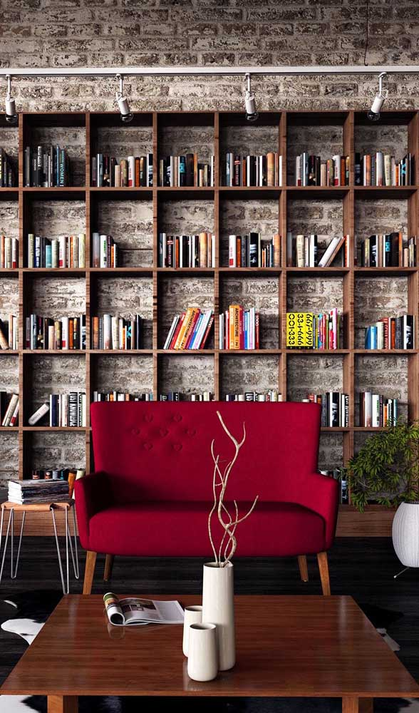 O sofá vermelho combinou muito bem com o estilo rústico da sala