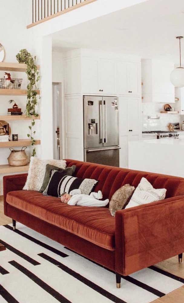 A base branca da decoração suaviza o efeito da cor vermelha do sofá