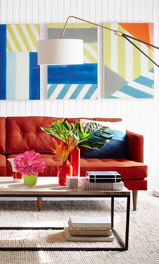 Essa sala de estar contemporânea apostou na combinação entre o sofá vermelho e os elementos de cores complementares, como o azul e o verde