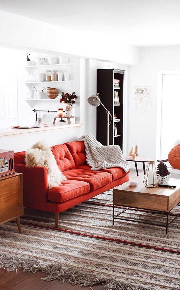 Conforto, estilo e elegância se unem nesse sofá vermelho colocado em uma sala de base branca