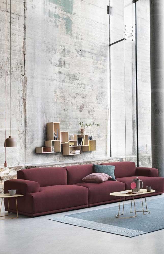 A sala de pé direito duplo trouxe um sofá vermelho de três lugares com a proporção ideal do ambiente