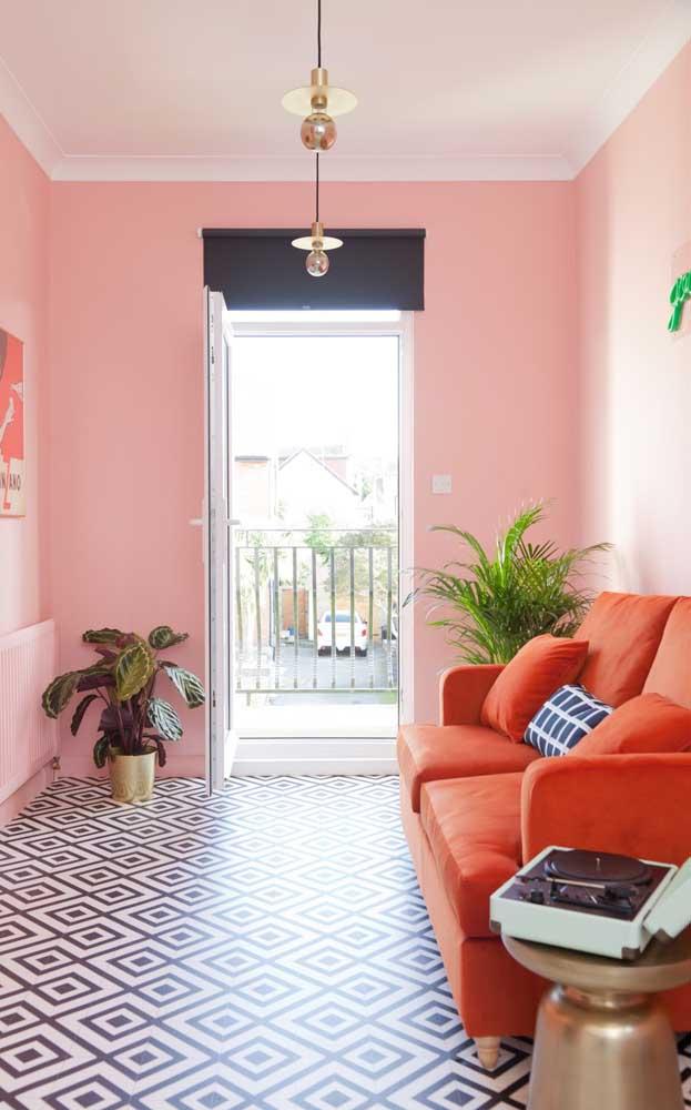 Que sala de estar mais aconchegante! As paredes em rosa claro são o pano de fundo perfeito para o sofá vermelho
