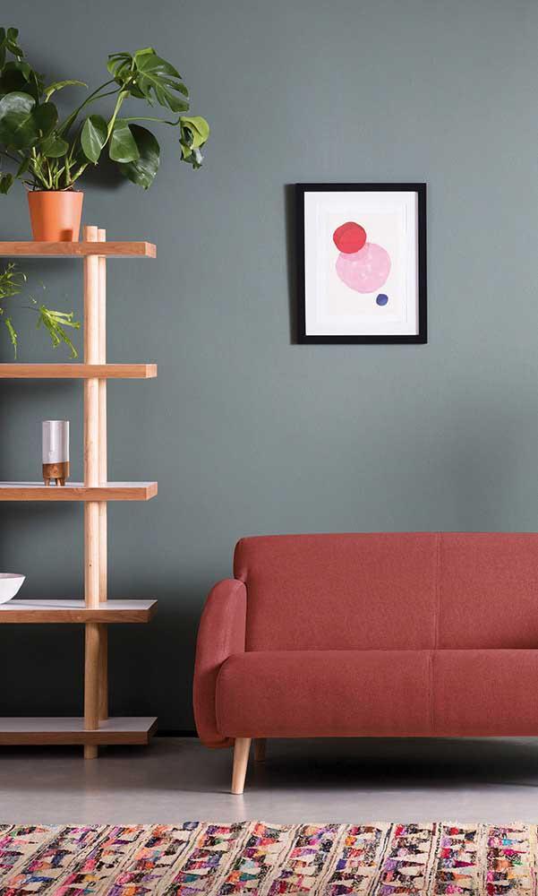 A parede cinza recebeu muito bem o sofá vermelho, revelando uma composição moderna e original