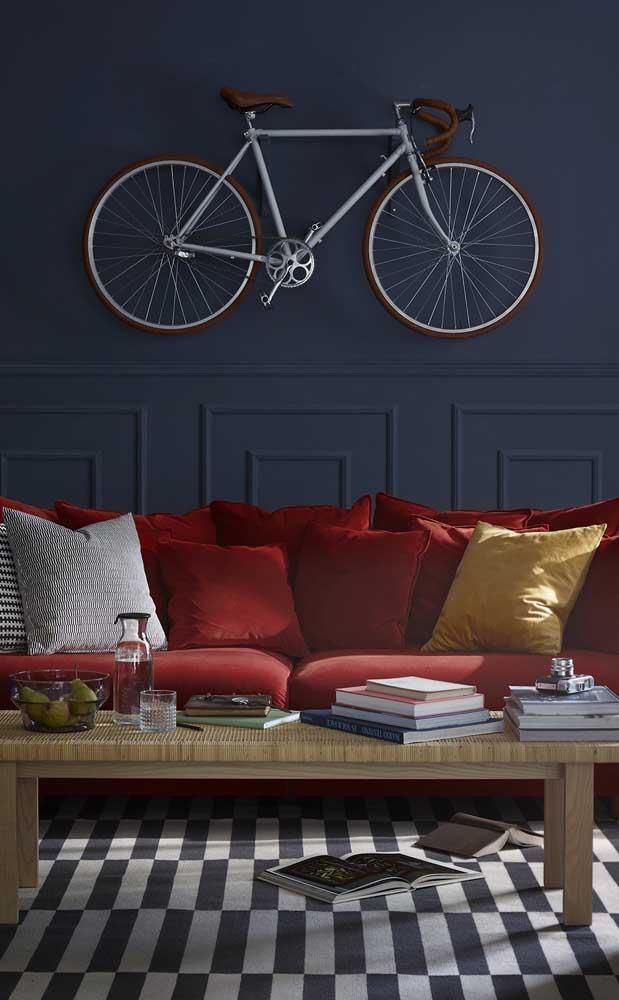 Um arraso a combinação entre parede azul com boiseries e o sofá vermelho