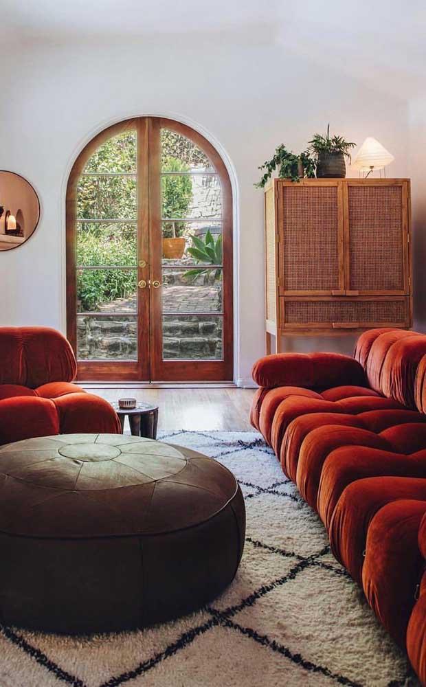 Para combinar com o sofá vermelho de veludo, um tapete estilo marroquino