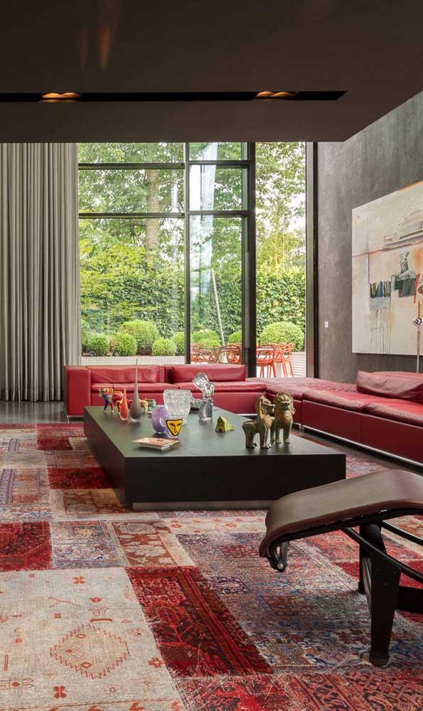 A sala de estar gigante pedia por um sofá tão grande quanto; o vermelho do estofado arremata a decor