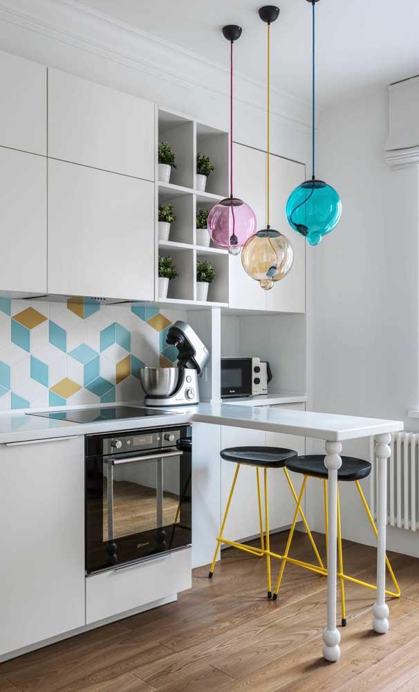 A cozinha americana branca se tornou o pano de fundo perfeito para a inserção de peças coloridas