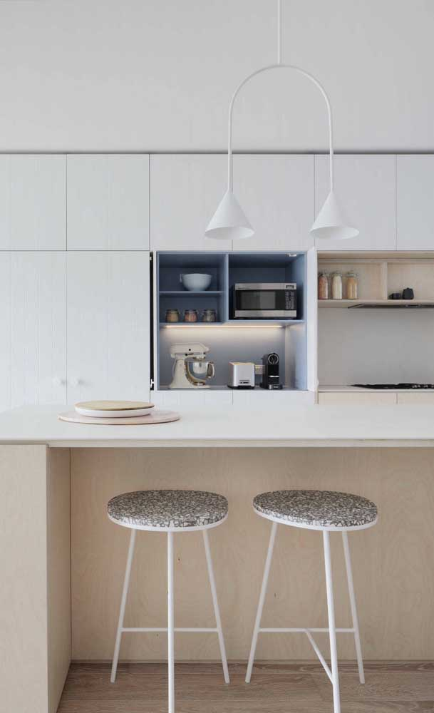 A luminária sobre o balcão da cozinha americana decora e ilumina