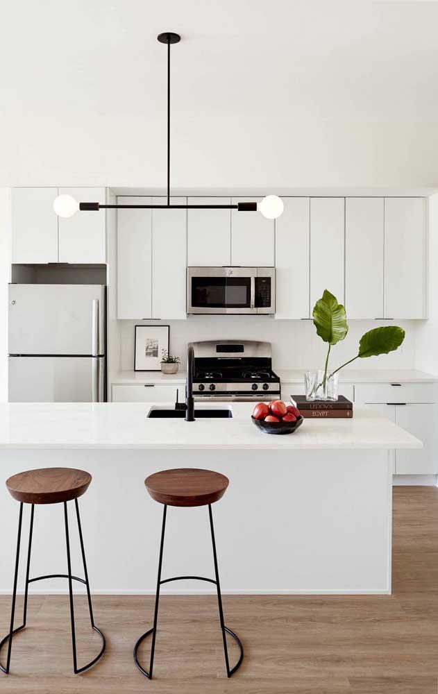O branco dessa cozinha americana foi levemente contrastado pelos detalhes em preto e em tom de madeira