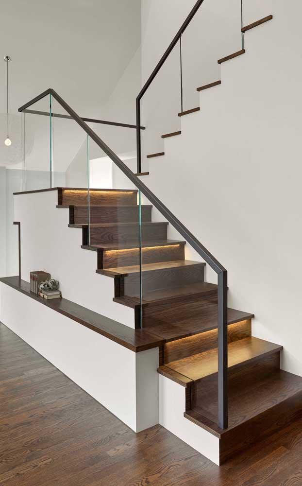 Escada moderna de alvenaria com degraus em madeira e guarda corpo de vidro, mas o charme fica mesmo por conta das fitas de LED