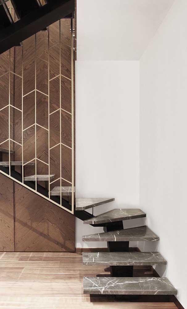 Escada moderna flutuante feita em mármore com um guarda corpo dourado super elegante