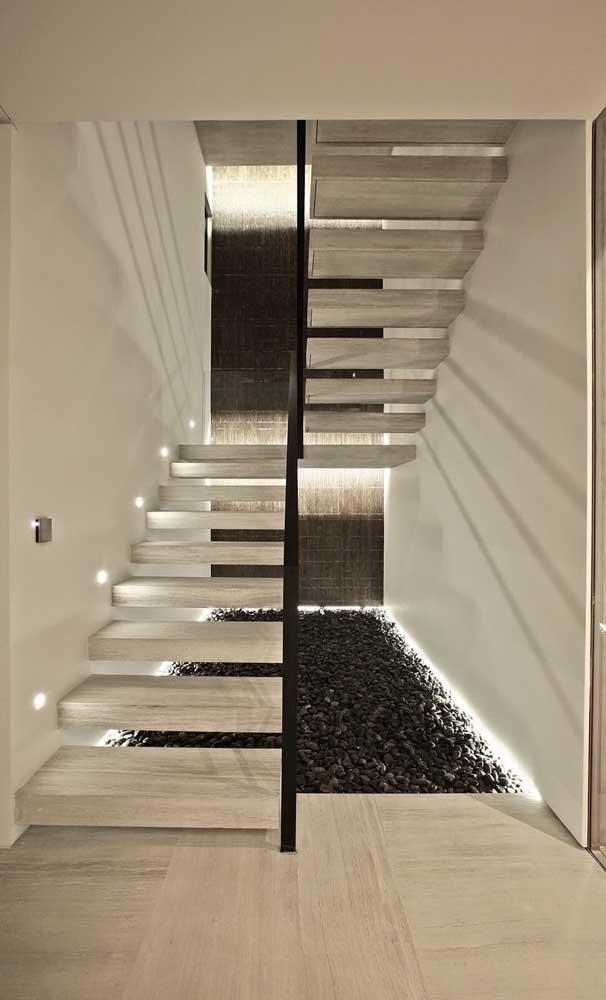 Escada moderna em U com pequenos spots de luz na lateral de cada degrau