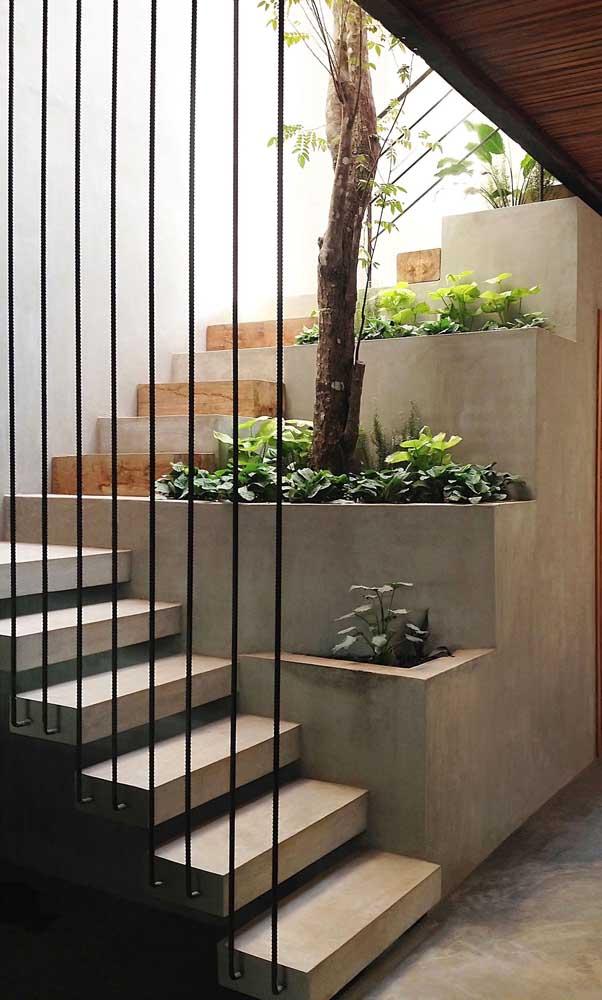 No primeiro patamar, a escada ganhou degraus de concreto e formato flutuante; já no segundo nível, os degraus se intercalam entre o concreto e a madeira em uma estrutura sólida