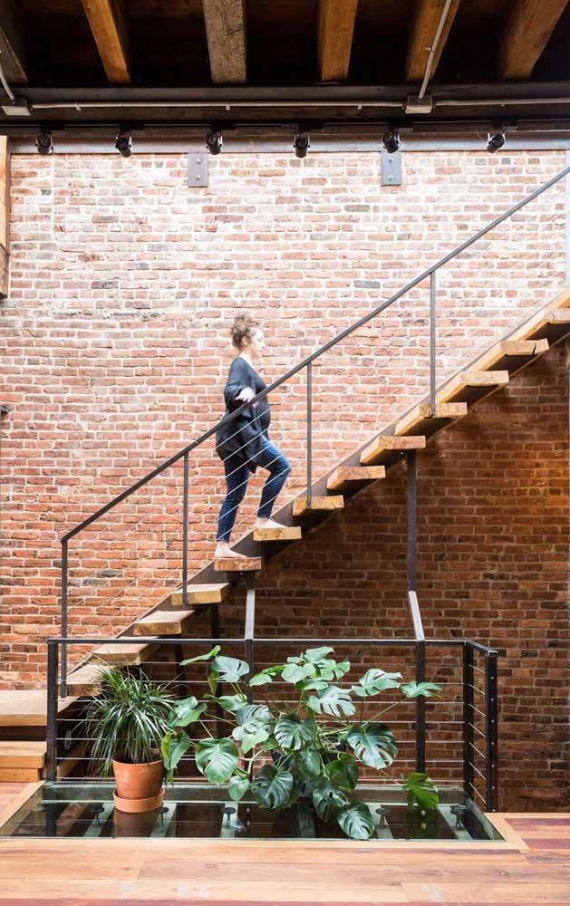 A parede de tijolinhos se revelou o fundo perfeito para a escada moderna de aço e madeira