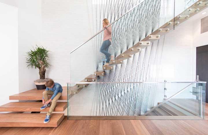 Escada flutuante de madeira com um guarda corpo de vidro quase invisível