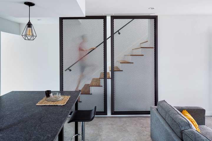 "Mesmo escondida atrás do ""biombo"" de aço, a escada moderna revela sua beleza mesclada entre a madeira e a alvenaria"