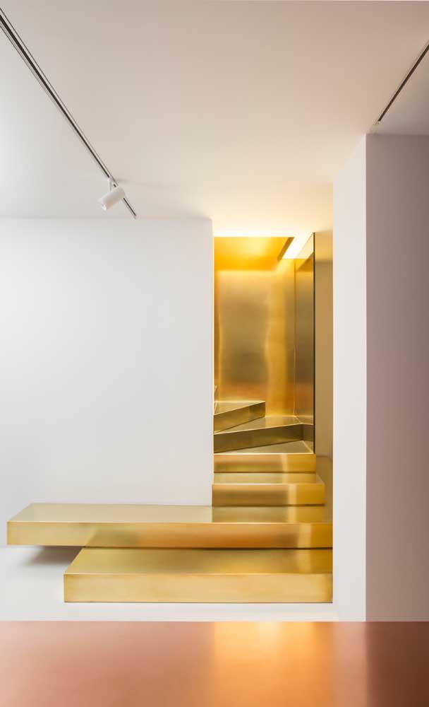 Que luxo essa escada moderna toda dourada; os degraus parecem barras de ouro