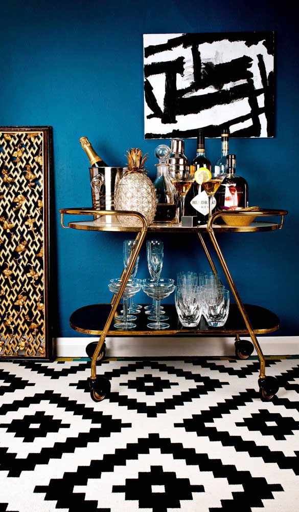 Carrinho bar dourado para contrastar com o chão em preto e branco