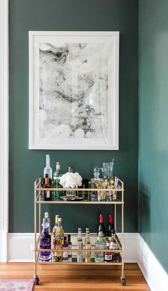 Linda composição entre o carrinho bar dourado e a parede verde