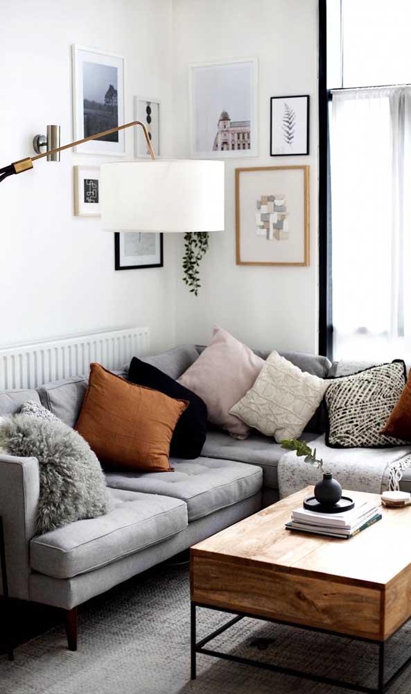 Quadros, almofadas e uma luminária para atrair toda atenção: elementos selecionados a dedo compõe essa pequena sala de estar