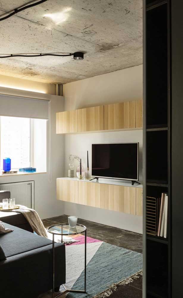 O toque industrial dessa sala de estar pequena ficou por conta do teto e do piso em cimento queimado