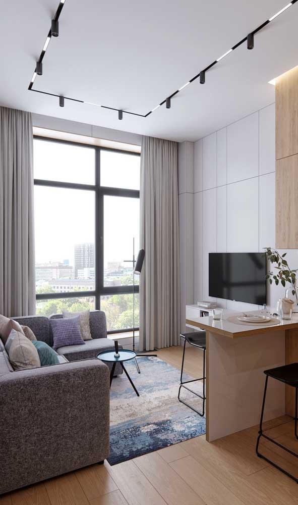 Nessa sala de estar, os spots direcionáveis no teto mantem a iluminação sempre perfeita