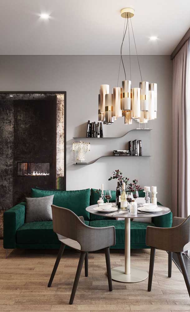 Um sofá verde glamouroso para a sala de estar pequena integrada à sala de jantar