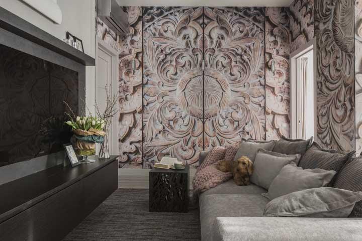 Destaque uma das paredes da sala de estar pequena com papel de parede ou adesivo