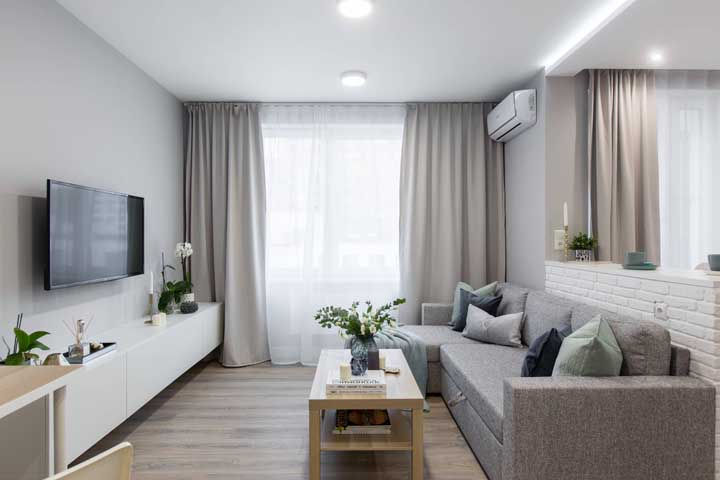 Móveis alongados, como o rack e o sofá da imagem, garantem a sensação de profundidade e continuidade do ambiente