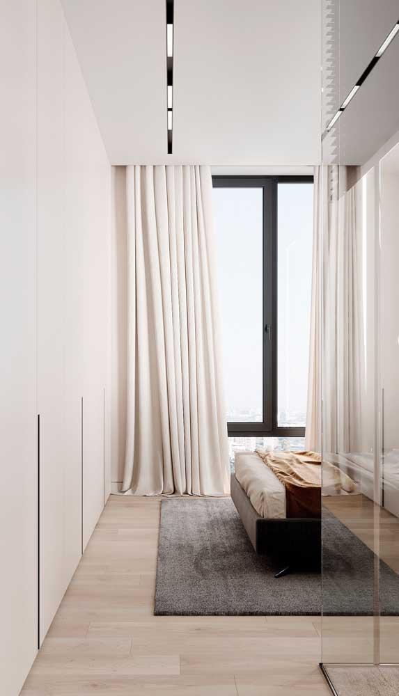 Aqui nesse quarto de casal, a grande janela de alumínio foi coberta pela cortina de tecido claro