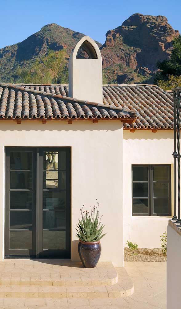 Portas e janelas de alumínio se combinam nessa fachada de casa de estilo mediterrâneo