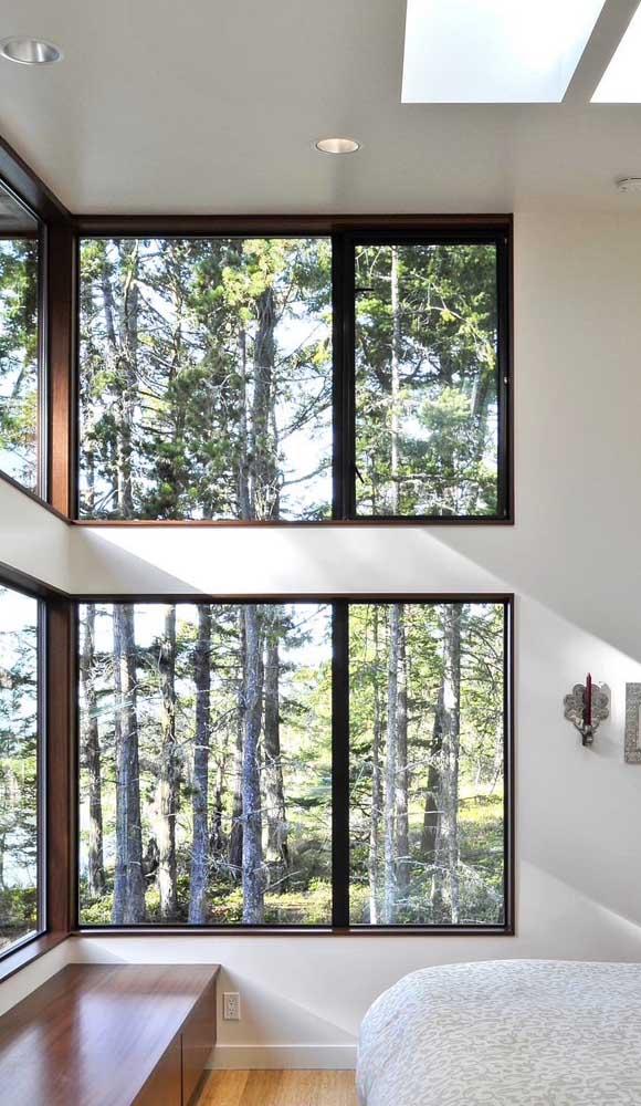 Nesse quarto de casal, as janelas de alumínio revestem grande parte da parede