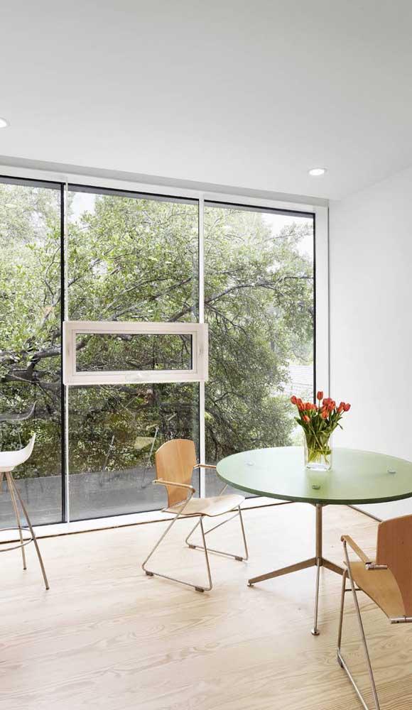 Sala de jantar com janela de alumínio inteiriça favorecendo a contemplação da paisagem externa