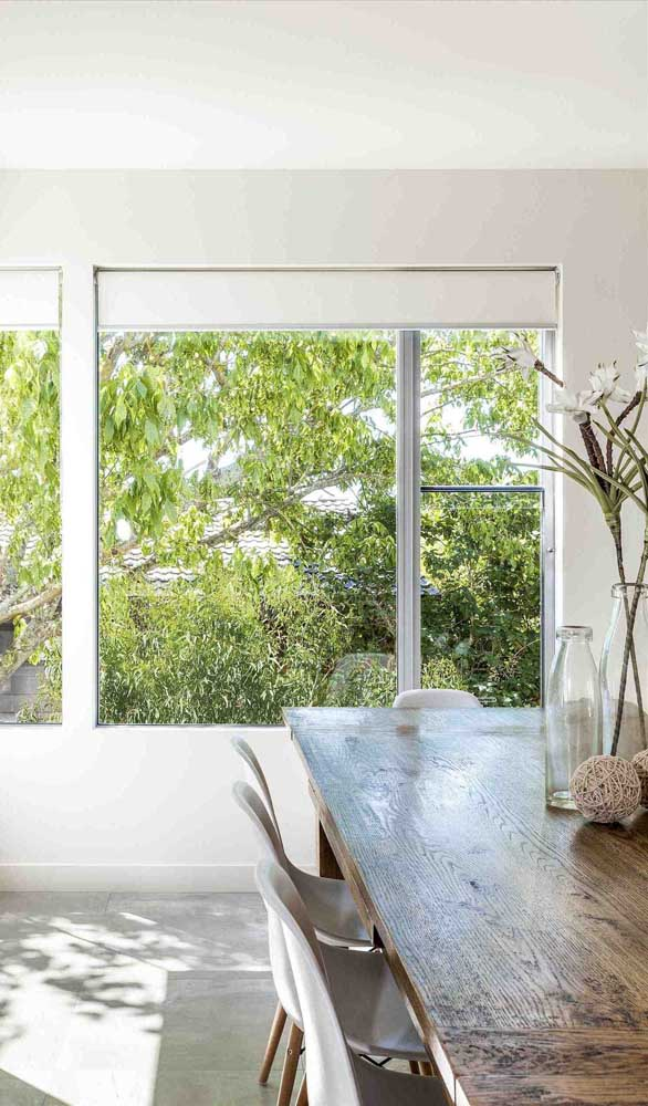 Sala de jantar com janela grande de alumínio protegida pela persiana