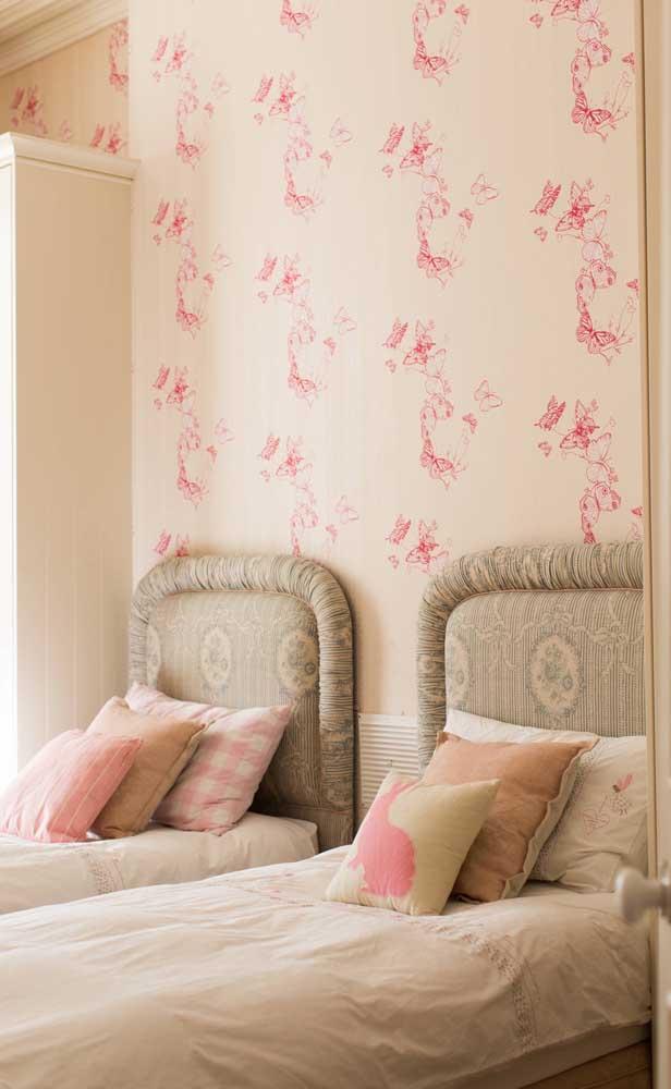 Inspiração de quarto de gêmeos feminino. Destaque para o papel de parede delicado e a cabeceira almofadada