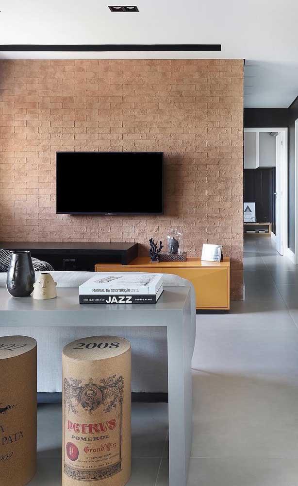 A parede de tijolinhos se tornou o painel dessa sala de estar com rack de madeira