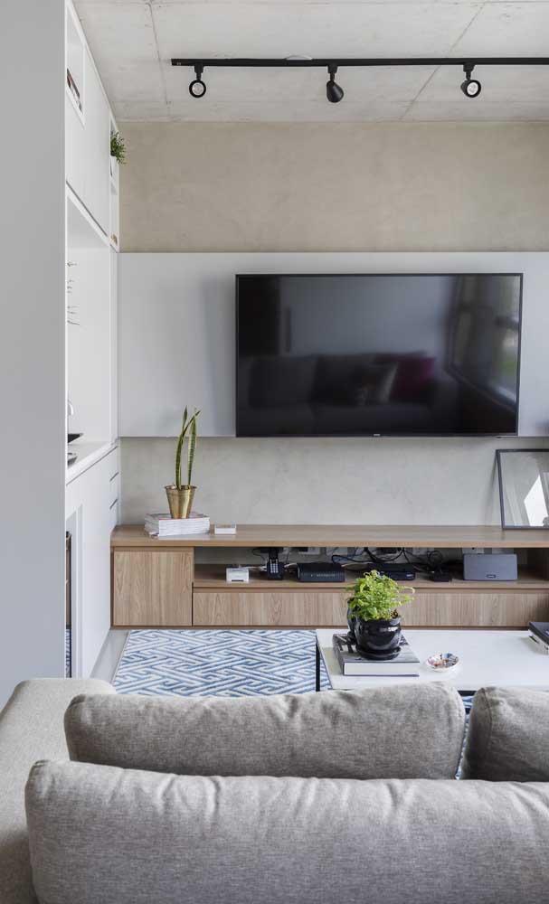 A faixa de MDF branco se torna o painel para a TV dessa sala