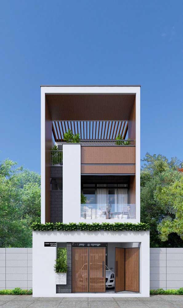 Casa sobrado com muro moderno de alvenaria combinado ao portão de madeira