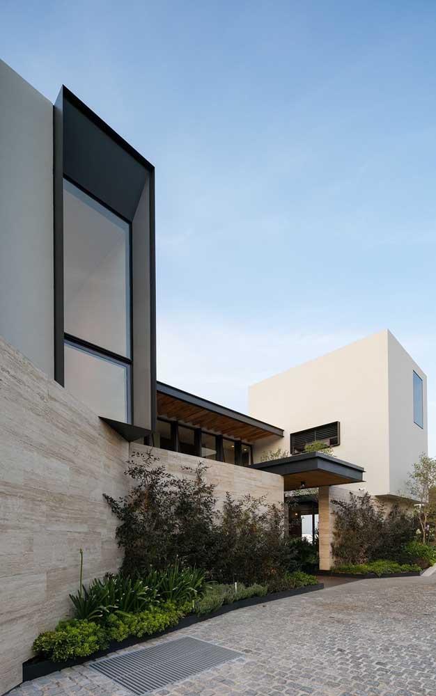 Muro moderno revestido com pedras. Para dar o toque final na fachada, um lindo canteiro na calçada