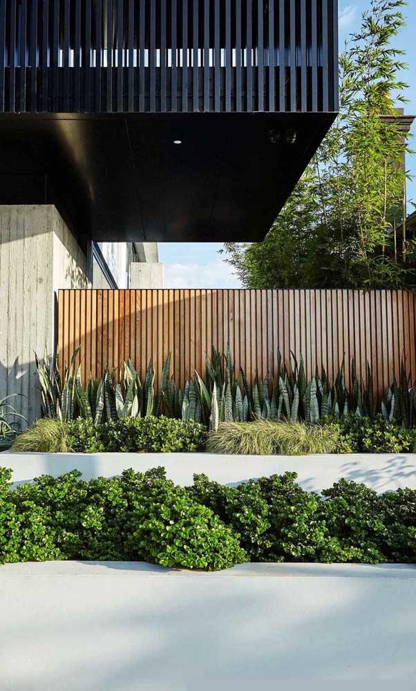 Aqui, o projeto de muro moderno inclui madeira e um canteiro bem verde