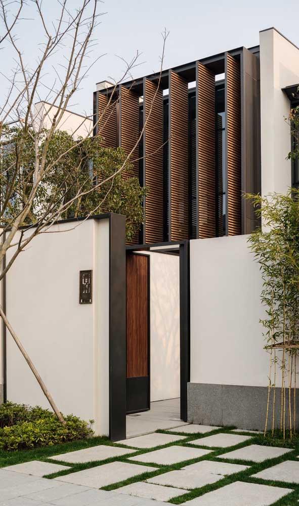 Muro moderno de alvenaria valorizado pelo canteiro na calçada