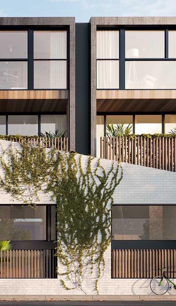 Mix de materiais para esse muro moderno: tijolinhos, madeira, metal e vidro